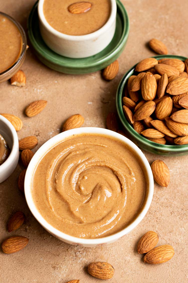 Raw Almond Butter Recipe, homemade almond butter recipe, almond butter in a serving bowl with some whole almonds