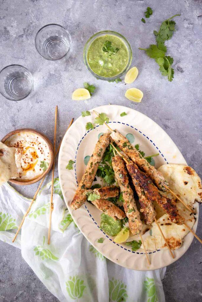 Seekh kebab with mint chutney and tzatziki sauce. chicken seekh kebab, Seekh kebab up close food pbotography, chicken seekh kebab