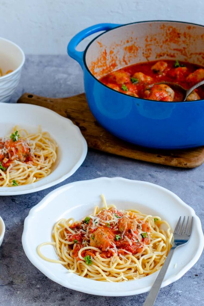 spaghetti sauce with chicken meatballs served over spaghetti in pasta bowls